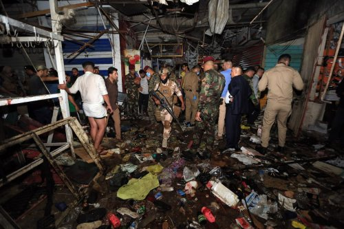Iraqi security forces and citizens inspect the site after a blast at Al-Wahilat market in Sadr district of Baghdad, Iraq on July 19, 2021. It is reported that 22 were killed and 47 injured. ( Murtadha Al-Sudani - Anadolu Agency )