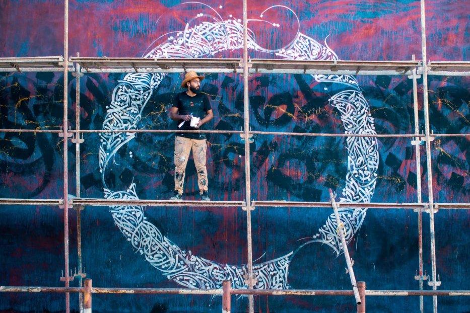 Belal Khaled works on his calligraffiti project [Majdi Fathi]