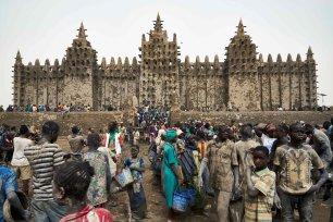 People take part in the annual rendering of the Great Mosque of Djenne in central Mali on April 28, 2019 [MICHELE CATTANI/AFP via Getty Images]