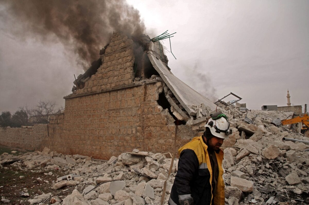 A White Helmet rescue worker walks past a house that was destroyed during an airstrike in the western countryside of Aleppo on February 12, 2020 [AAREF WATAD/AFP via Getty Images]