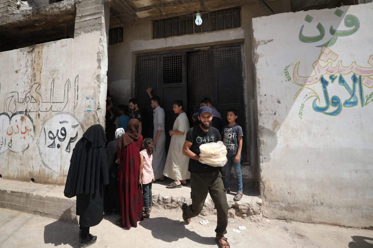 Syrians buy bread in the town of Binnish in the country's northwestern Idlib province on June 9, 2020 [OMAR HAJ KADOUR/AFP via Getty Images]