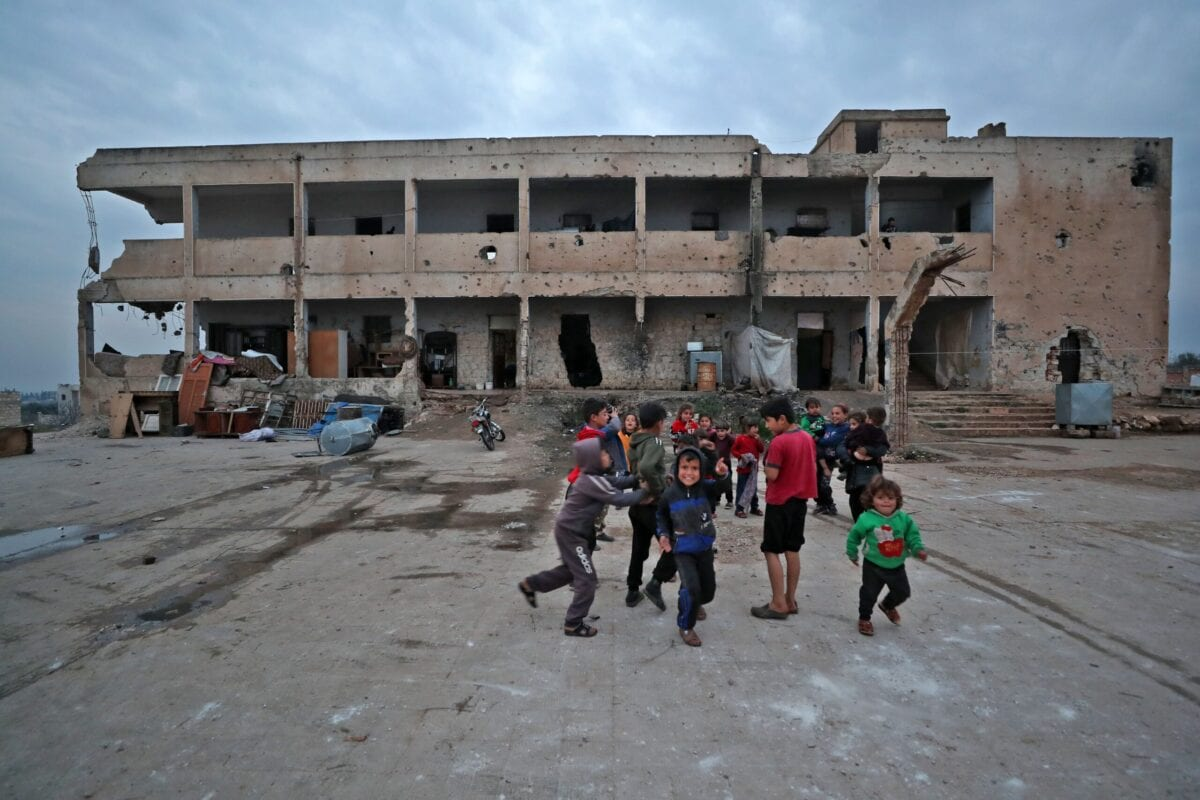 Children of displaced families living in an abandoned damaged school building, play in the yard in Binnish in Syria's northwestern province of Idlib, on March 2, 2021 [OMAR HAJ KADOUR/AFP via Getty Images]