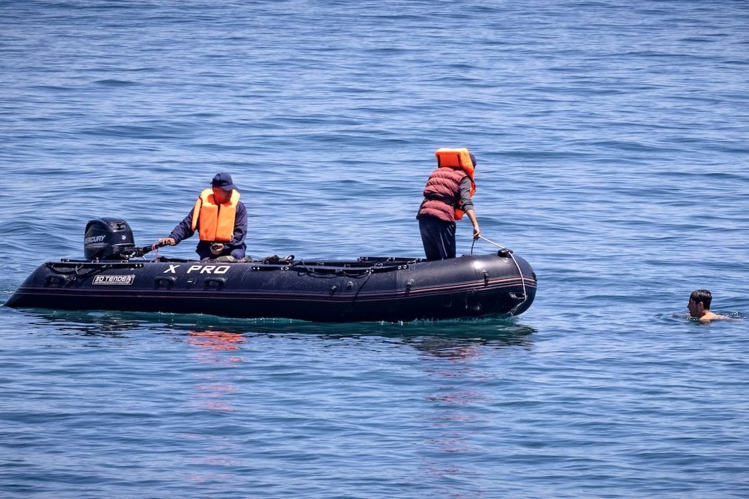Royal Moroccan Navy officers intercept migrants in the water at the border between Morocco and the Spanish enclave of Ceuta on May 19, 2021 in Fnideq. [FADEL SENNA/AFP via Getty Images]