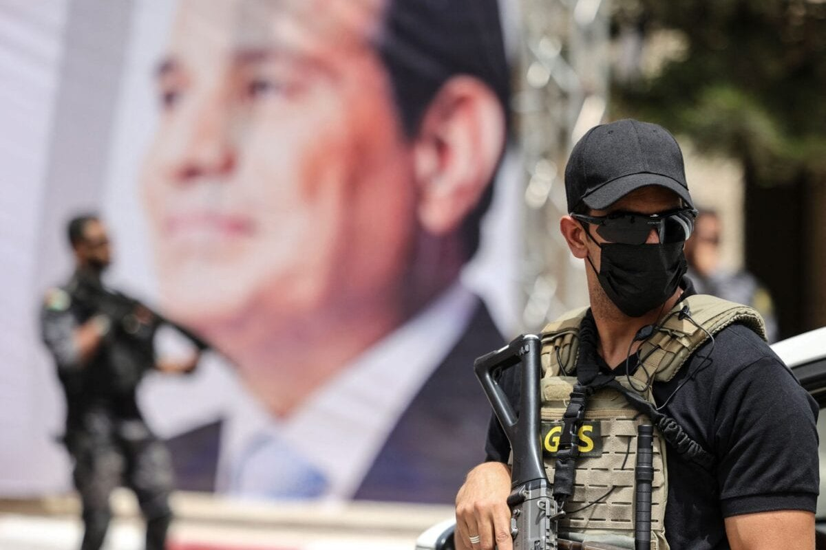 An Egyptian intelligence security detail member stands guard near a banner showing President Abdel Fattah al-Sisi on May 31, 2021 [MAHMUD HAMS/AFP via Getty Images]