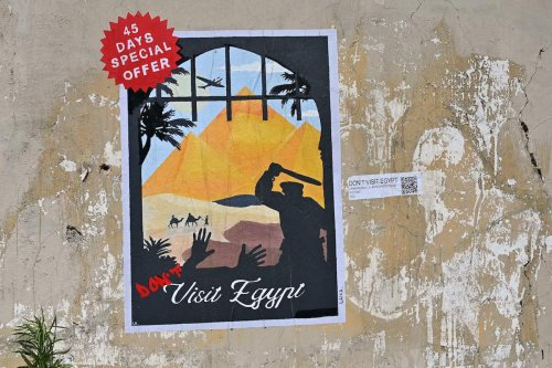 """A poster by Italian street artist Laika, entitled """"Don't visit Egypt"""", is pictured on a wall near the Egyptian embassy on June 16, 2021 in Rome in protest against the recent extension of the detention in Egypt of a 29-year-old Egyptian student Patrick Zaki. [ALBERTO PIZZOLI/AFP via Getty Images]"""
