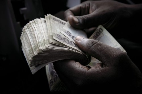 A person counts South Sudanese pound banknotes in Juba, South Sudan, on Sunday, June 6, 2021 [Adrienne Surprenant/Bloomberg via Getty Images]