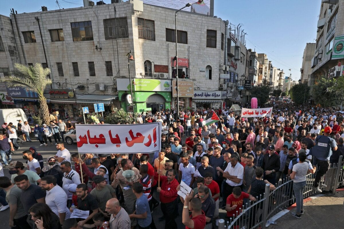 """Palestinian demonstrators lift banners in Arabic addressing Palestinian President Mahmoud Abbas which read """"Leave"""" during a rally in Ramallah city in the occupied West Bank on July 3, 2021 [ABBAS MOMANI/AFP via Getty Images]"""