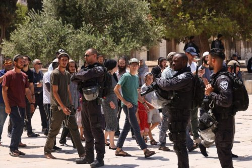 Members of the Israeli security forces stand guard, as a group of Orthodox Jews enter the al-Aqsa mosque compound in Jerusalem, on July 18, 2021 [AHMAD GHARABLI/AFP via Getty Images]