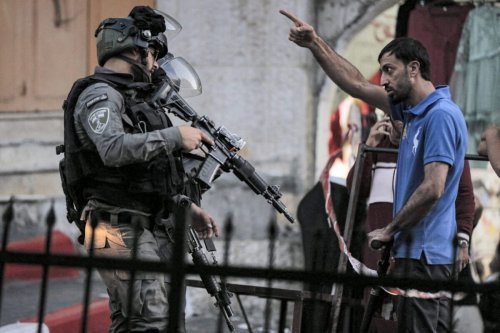 A Palestinian man argues with Israeli border guards blocking a street for a procession of religious Jews on Tisha B'Av marching towards the shrine of Atnaeil Ben Kinaz in the flashpoint city of Hebron in the Israeli-occupied West Bank on June 18, 2021 [MOSAB SHAWER/AFP via Getty Images]