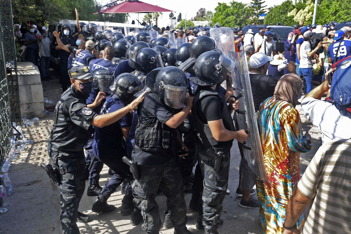 Tunisian security officers hold back protesters outside the parliament building in the capital Tunis on 26 July 2021, following a move by the president to suspend the country's parliament and dismiss the Prime Minister. [FETHI BELAID/AFP via Getty Images]