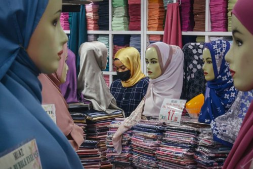A muslim woman wears a protective face mask as she shops for headscarves at a Ramadan bazaar on April 29, 2021 [Annice Lyn/Getty Images]