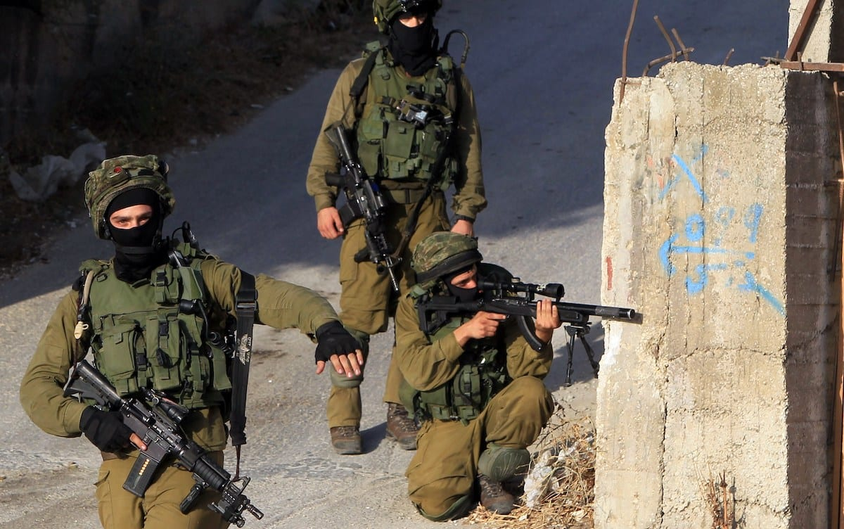 Israeli soldiers hold a position in a street, east of the West Bank city of Nablus, on October 3, 2015, as they search for the suspected killers of a Jewish settler couple. [JAAFAR ASHTIYEH/AFP via Getty Images]
