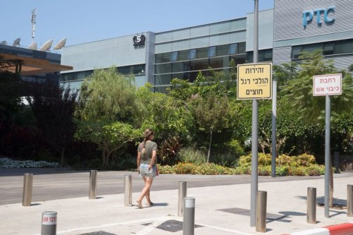An Israeli woman walks in front of the building housing the Israeli NSO group, on August 28, 2016, in Herzliya, near Tel Aviv [JACK GUEZ/AFP via Getty Images]