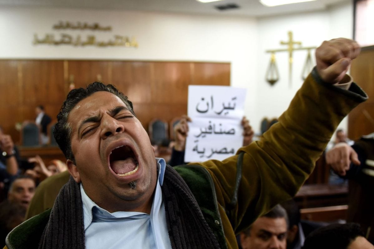 Egyptians react on December 19, 2016 at the high administrative court as a judge announces the postponing of a court ruling in the case of two Red Sea islands to January 16, 2017, in the capital Cairo. The writing in Arabic reads ''Tiran and Sanafir are Egyptian''. [MOHAMED EL-SHAHED/AFP via Getty Images]