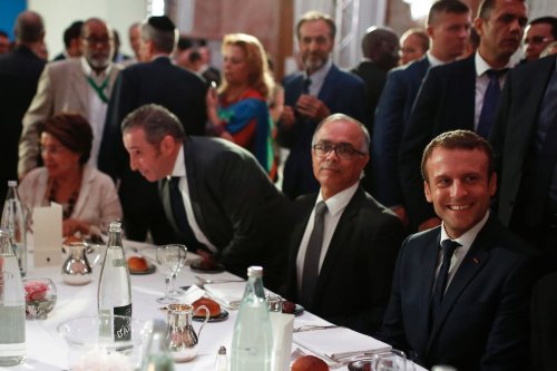 French President Emmanuel Macron (R), flanked by Moroccan ambassador to France Chakib Benmoussa (2ndR) smiles as he attends a dinner organised by the French Council of the Muslim Faith (CFCM) to break the fast of Ramadan, in Paris, on 20 June 2017. [BENJAMIN CREMEL/AFP via Getty Images]