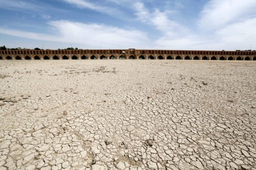 """A general view shows the """"Si-o-Se Pol"""" bridge (33 Arches bridge) over the Zayandeh Rud river in Isfahan, which now runs dry due to water extraction before it reaches the city on April 11, 2018. The 295 metre long bridge was completed in 1596 by Iranian Safavid king, Shah Abbas the Great (Shah Abbas l). / AFP PHOTO / ATTA KENARE (Photo credit should read ATTA KENARE/AFP via Getty Images)"""