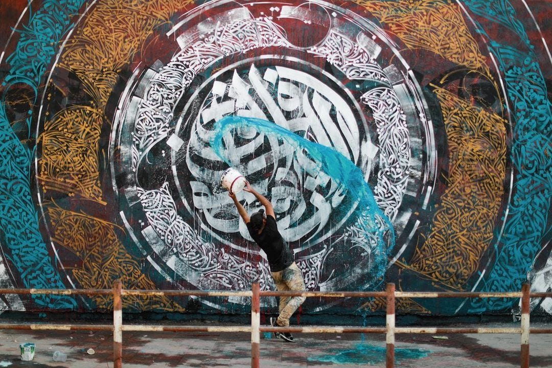 Belal Khaled puts the finishing touches on a 50-metre long artwork in Gaza in July 2021 [Majdi Fathi]