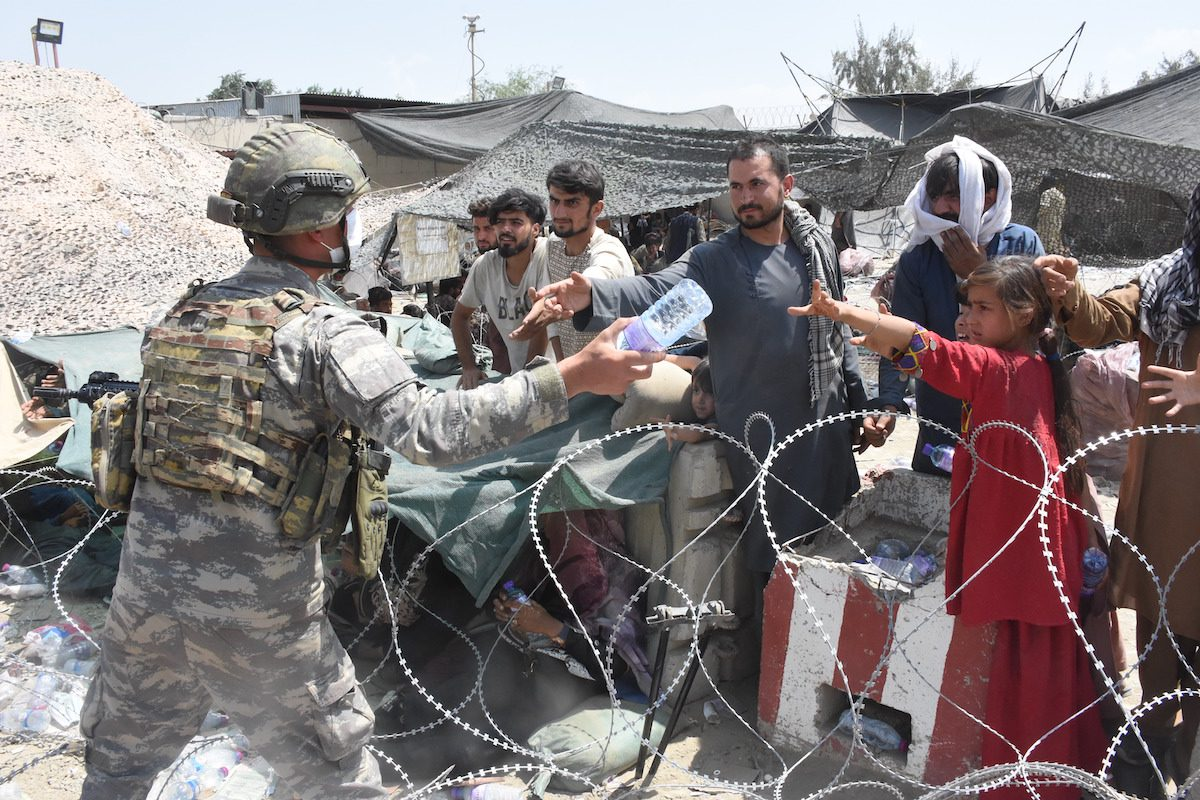 """KABUL, AFGHANISTAN - AUGUST 23: Soldiers of Turkish Task Force in Afghanistan are on duty in and around Hamid Karzai International Airport to help people who are waiting for evacuation, in Kabul, Afghanistan on August 23, 2021. The soldiers are also working on the coordination of the evacuation in a headquarters building named """"Ankara"""". ( Aykut Karadağ - Anadolu Agency )"""