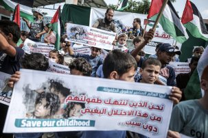 Palestinian children hold banners as they gather to release balloons during a protest against Israeli blockade in front of Beit Hanoun border crossing in Gaza City, Gaza on August 24, 2021. [Ali Jadallah - Anadolu Agency]