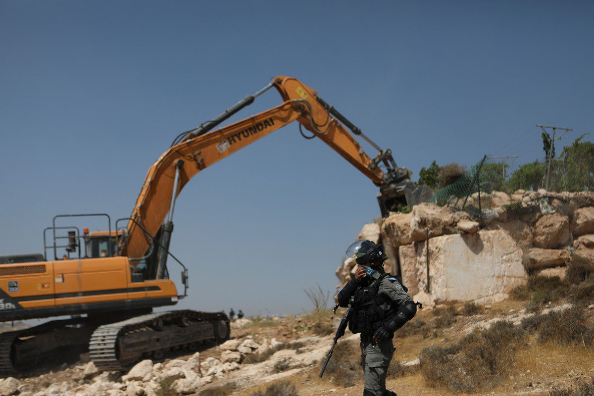 Israeli bulldozers backed by police forces tear down a car maintenance shop belonging to a Palestinian family in area of Harayik, Hebron, West Bank on 25 August 2021. [Mamoun Wazwaz - Anadolu Agency]