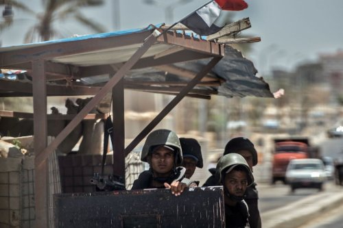 A picture taken on July 26, 2018 shows Egyptian policemen stand guarding a checkpoint on a road leading to the North Sinai provincial capital of El-Arish. [KHALED DESOUKI/AFP via Getty Images]