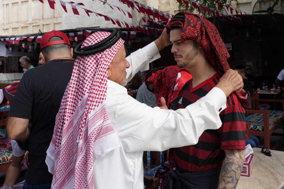 An old man helps Flamengo fan to wear the Arabic scarf at the Souq area ahead of the FIFA Club World Cup Final match between Flamengo and Liverpool FC on 21 December 2019 in Doha, Qatar. [Etsuo Hara/Getty Images]