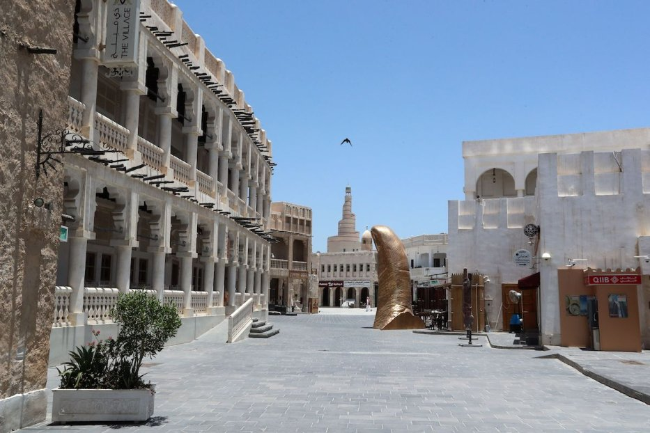 """People wearing protective gear walk by near a sculpture entitled """"Le Pouce"""" by French artist Cesar Baldaccini, at Qatar's touristic Souq Waqif bazar in the capital Doha, on 17 May 2020, as the country begins enforcing the world's toughest penalties for failing to wear masks in public while it battles one of the world's highest coronavirus infection rates. [KARIM JAAFAR/AFP via Getty Images]"""