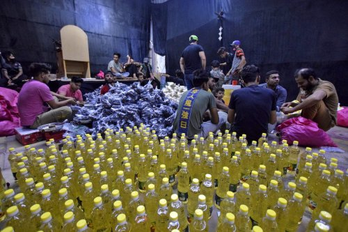 Iraqi volunteers prepare food aid to be distributed to the poor and needy in Nassiriyah, on 20 April 2021 [ASAAD NIAZI/AFP via Getty Images]