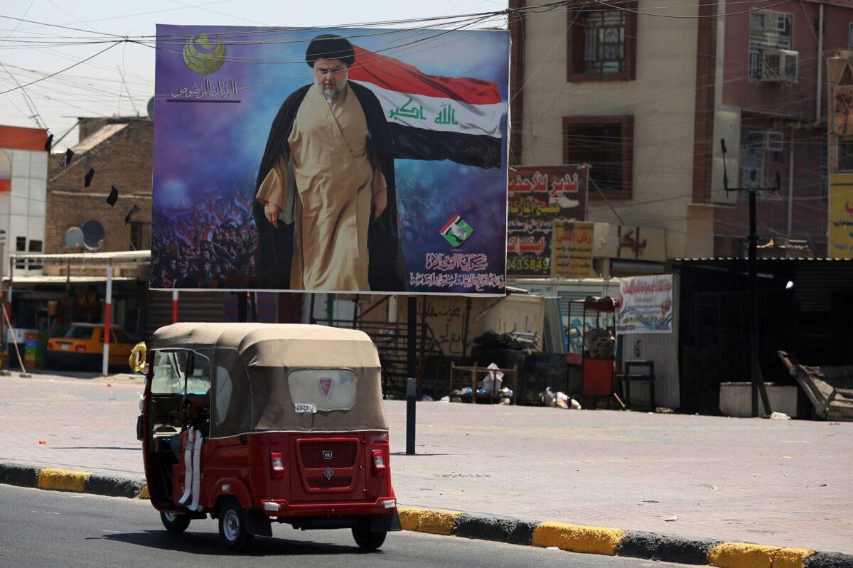 A tuktuk car drives past a large poster of Iraq's populist Shia Muslim cleric Moqtada Sadr, in Sadr City, east of the capital Baghdad, on July 15, 2021 [AHMAD AL-RUBAYE/AFP via Getty Images]