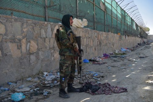 A Taliban fighter stands guard at the site of the August 26 twin suicide bombs, which killed scores of people including 13 US troops, at Kabul airport on August 27, 2021. (Photo by WAKIL KOHSAR / AFP) (Photo by WAKIL KOHSAR/AFP via Getty Images)
