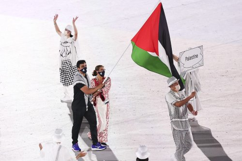 Flag bearers Dania Nour and Mohammed K H Hamada of Team Palestine lead their team during the Opening Ceremony of the Tokyo 2020 Olympic Games at Olympic Stadium on 23 July 2021 in Tokyo, Japan. [Maja Hitij/Getty Images]