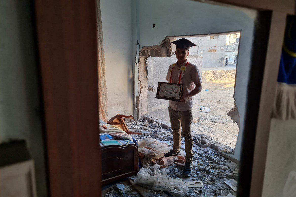 Palestinian student Yehya Al-Saqqa from Khan Yunis stands in his destroyed bedroom after he attained 94% in the Tawjihi exams. Al-Saqqa's home was partially destroyed by the Israeli bombing campaign on Gaz in May 2021, just one month before he sat the exams.