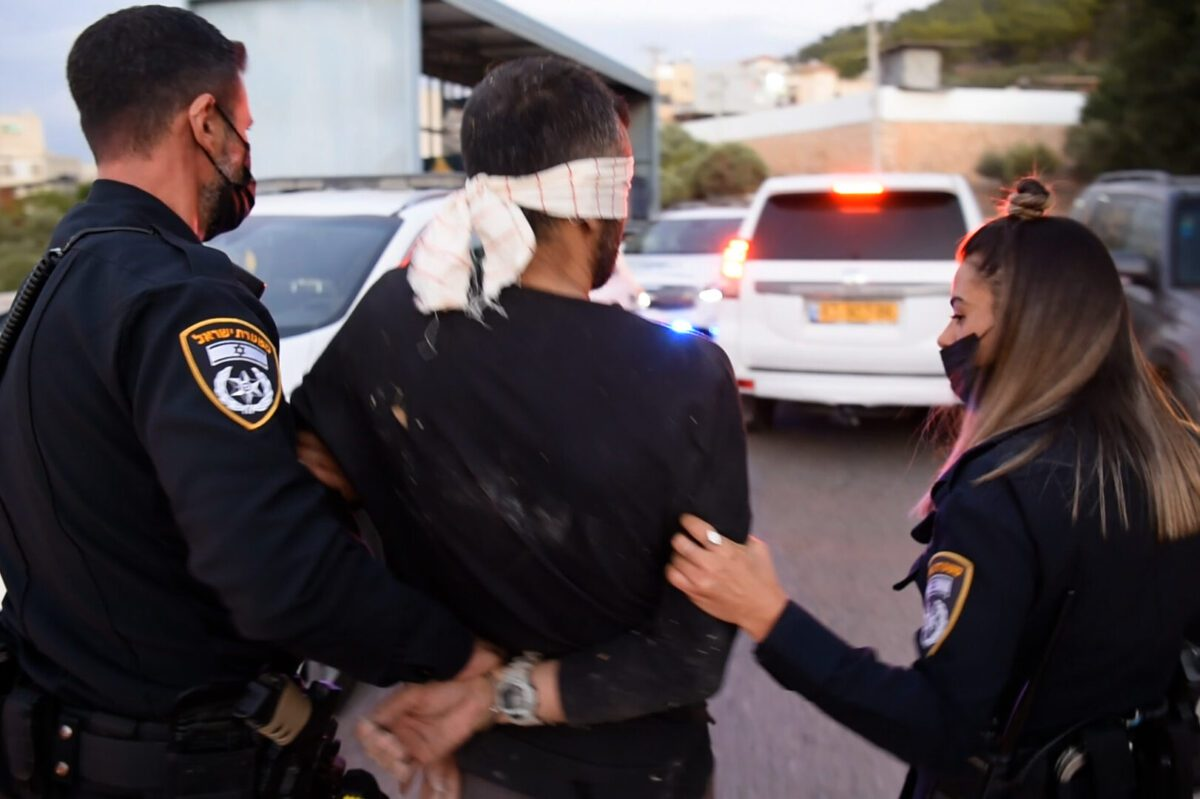 Israeli security forces take a Palestinian inmate into custody, one of the 6 escapees from Gilboa prison, after being arrested in Umm al-Ghanam town, Israel on September 11, 2021 [Israeli Police / Anadolu Agency]