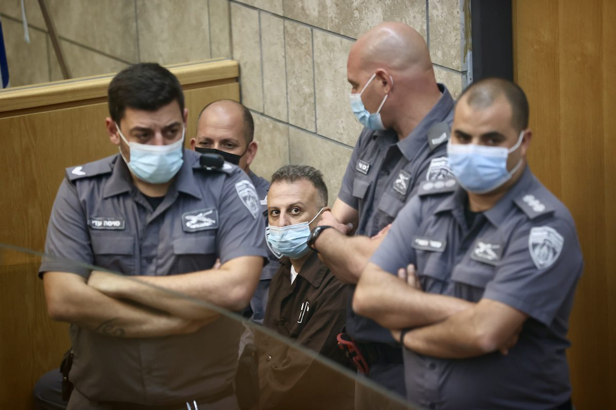 Palestinian escapee Yaqoub Qadri, one of the six escapees who escaped from a from a high-security Israeli Gilboa prison, is surrounded by Israeli police officers during his trial at the magistrates' court in the northern Israeli city of Nazareth, on 11 September 2021, following his recapture. [ Mostafa Alkharouf - Anadolu Agency ]