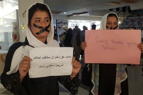 """Afghan women hold banners and taped their mouths as they gather to stage """"silent protest"""" for their education rights at the entrance of the shopping mall opposite the Ministry of Education, in Kabul, Afghanistan on September 19, 2021. ( Sayed Khodaiberdi Sadat - Anadolu Agency )"""