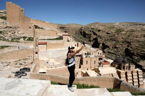 A tourist takes a 'selfie' against a view of the Greek Orthodox monastery of Saint Sabbas (Mar Saba), overlooking the Kidron valley, south of the West Bank biblical town of Bethlehem, on March 6, 2021 [HAZEM BADER/AFP via Getty Images]
