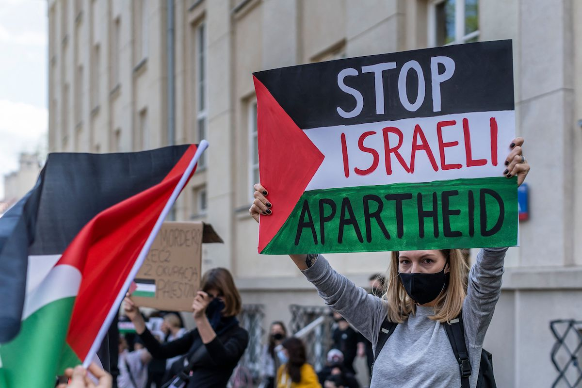 """A participant holds up a sign reading """"Stop Israeli Apartheid"""" during a protest in solidarity with the Palestinians called over the ongoing conflict with Israel in front of the Israeli embassy in Warsaw, 15 May 2021. [WOJTEK RADWANSKI/AFP via Getty Images]"""
