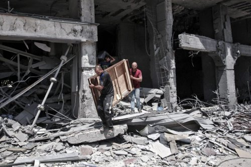 Palestinian men remove salvageable items from the bombarded Al-Jawhara Tower in Gaza City's Rimal neighbourhood on May 17, 2021 [ANAS BABA/AFP via Getty Images]