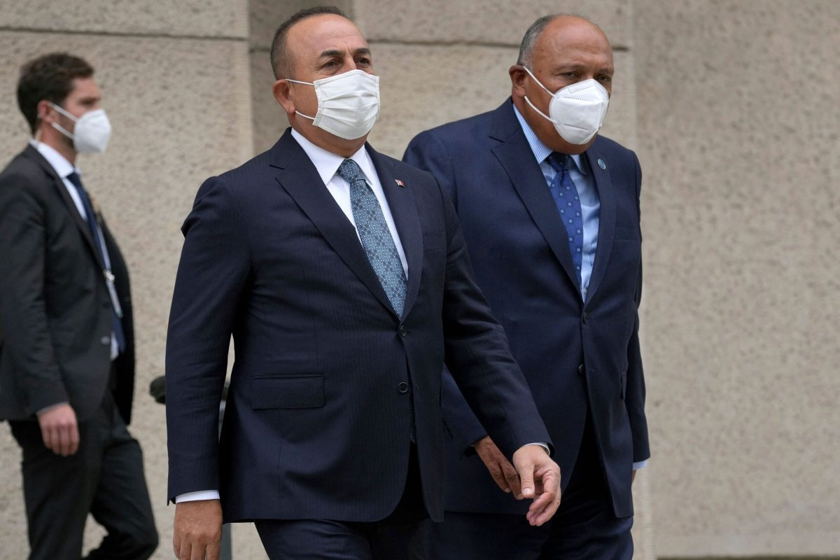 Turkish Foreign Minister Mevlut Cavusoglu (L) and his Egyptian counterpart Sameh Shoukry arrive for a group photo during the Second Berlin Conference on peace in Libya at the German Foreign Ministry in Berlin on June 23, 2021 [MICHAEL SOHN/POOL/AFP via Getty Images]