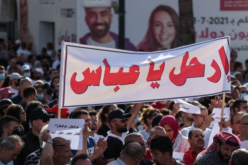 """Palestinians lift placards in Arabic which read """"What a situation: Occupation... deceit... arrest... assassination"""" as a banner addressing Palestinian President Mahmoud Abbas reads """"Leave"""" in Ramallah city in the occupied West Bank on July 3, 2021, as they rally for a protest denouncing the Palestinian Authority (PA) [ABBAS MOMANI/AFP via Getty Images]"""