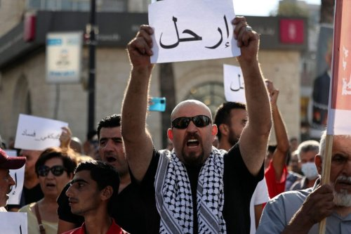 """A Palestinian demonstrator lifts a placard in Arabic addressing Palestinian President Mahmoud Abbas which reads """"Leave"""", during a rally in Ramallah city in the occupied West Bank on July 11, 2021 [ABBAS MOMANI/AFP via Getty Images]"""
