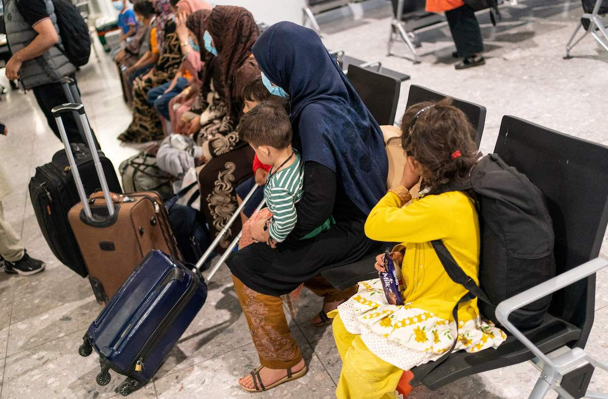 Afgan refugees wait to be processed after arriving on an evacuation flight from Afghanistan, at Heathrow Airport, London on 26 August 2021. [DOMINIC LIPINSKI/POOL/AFP via Getty Images]