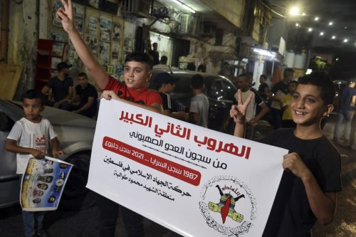 """Palestinian youths carry a poster by militant group Islamic Jihad reading in Arabic: """"the second great escape from the prisons of the Zionist enemy [JAAFAR ASHTIYEH/AFP via Getty Images]"""