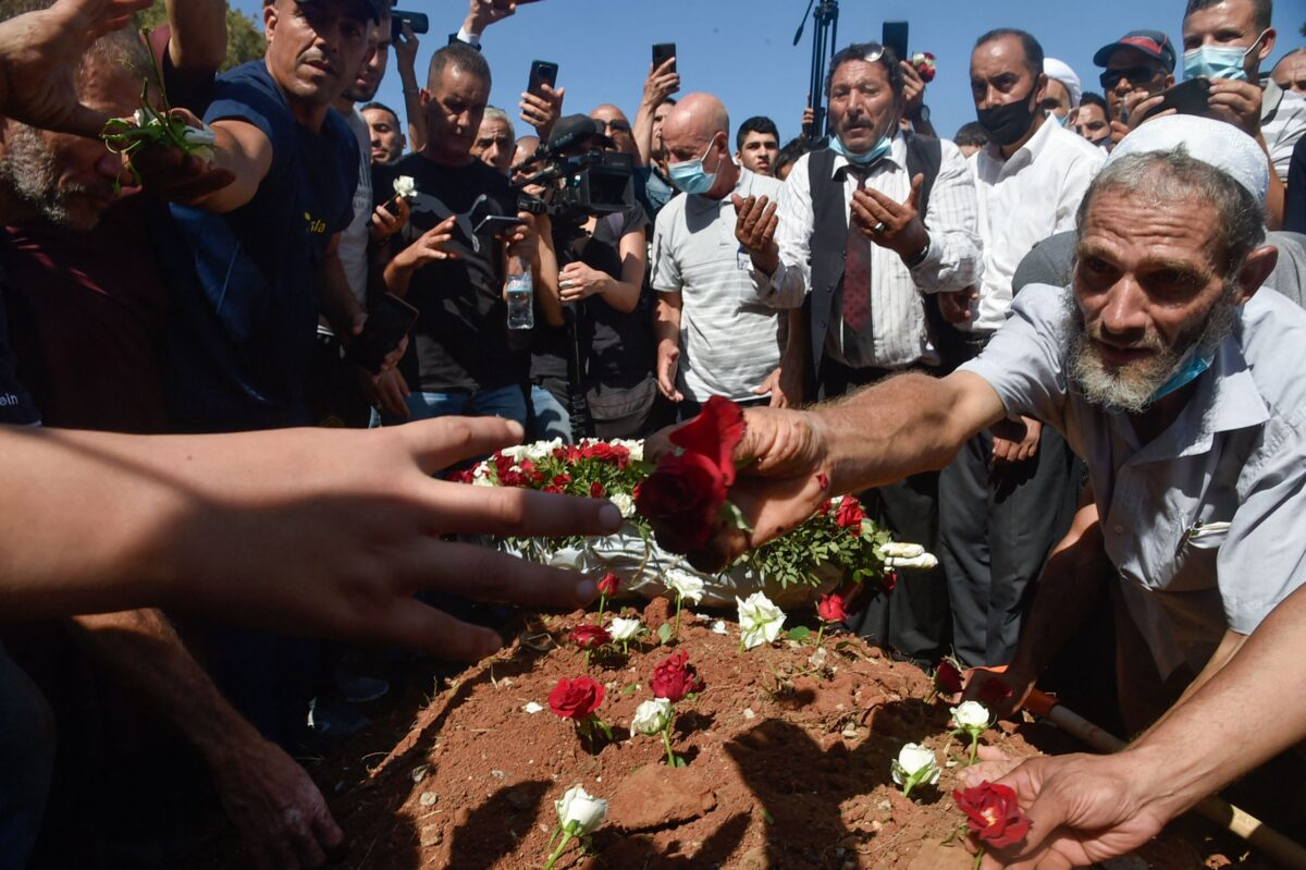 Algerians place roses on the tomb of former president Abdelaziz Bouteflika during his funeral at the El-Alia cemetery in the capital Algiers on September 19, 2021 [RYAD KRAMDI/AFP via Getty Images]