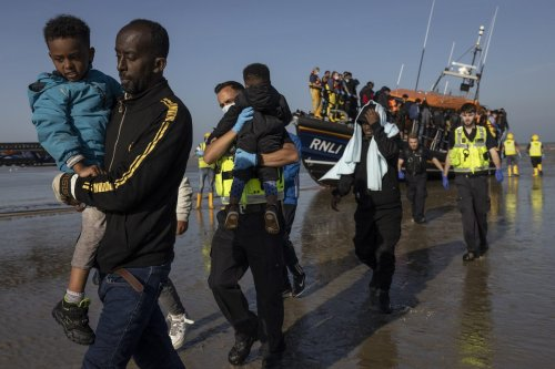 A group of migrants arrive via the RNLI (Royal National Lifeboat Institution) on Dungeness beach on 7 September 2021 in Dungeness, England. [Dan Kitwood/Getty Images]