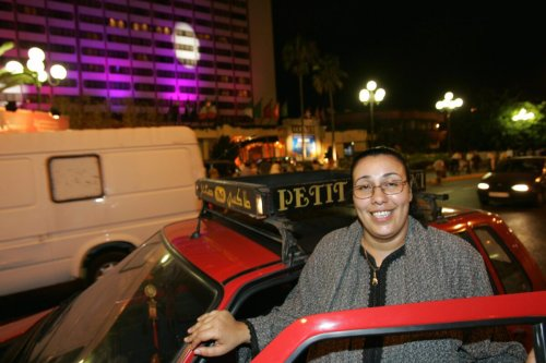 """Karima, a woman taxi driver smiles as she gets into her typical """"Petit Taxi """" vehicle during in Casablanca, 22 July 2005 [ABDELHAK SENNA/AFP via Getty Images]"""