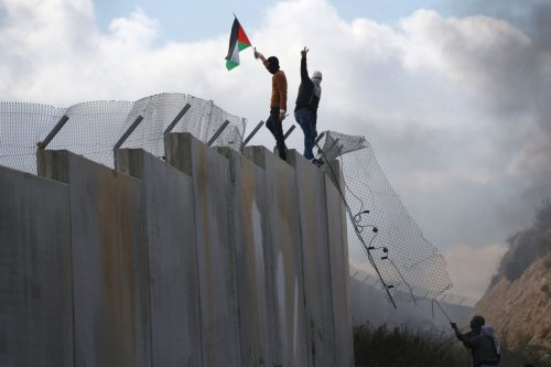 Palestinians climb on top of Israel's controversial separation wall between the West Bank village of Bilin near Ramallah and the Israeli settlement of Modiin Ilit during a demonstration against settlements in the area, on February 17, 2017 [ABBAS MOMANI/AFP via Getty Images]