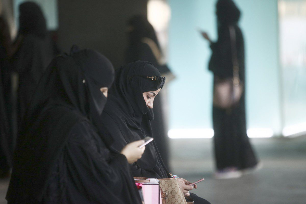 Shoppers check their smartphones whilst waiting for transport in Riyadh, Saudi Arabia, on 2 December 2016 [Simon Dawson/Bloomberg/Getty Images]