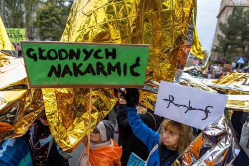 People take part in a protest rally in solidarity with migrants who have been pushed back at Poland's border with Belarus in Warsaw, 17 October 2021 [WOJTEK RADWANSKI/AFP/Getty Images]