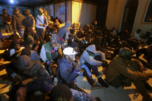 Migrants sait on the floor at a detention centre in Libya's Tajoura on November 29, 2019 [MAHMUD TURKIA/AFP via Getty Images]